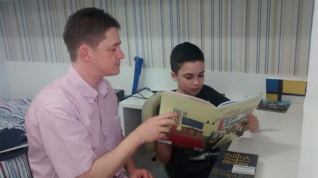 Família lendo o álbum na Paróquia Sant'Ana (Abranches - Curitiba-PR)
