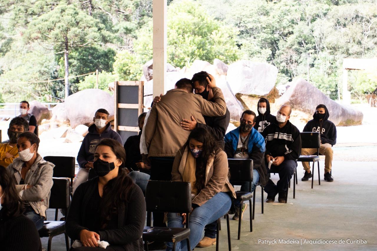 Pai e filho abraçados após o testemunho emocionado (Foto: Patryck Madeira/ Arquidiocese de Curitiba)